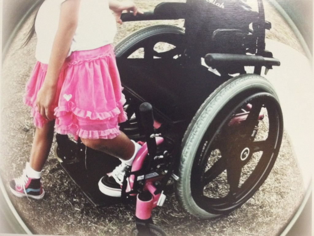 young girl stepping off wheelchair