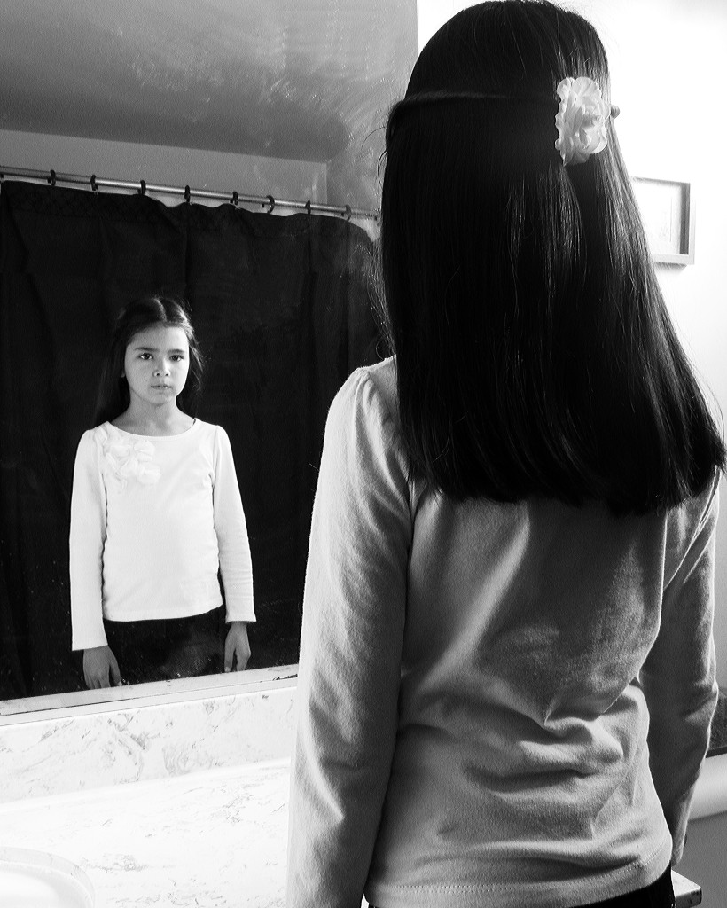 Young girl looking at herself in the mirror black & white