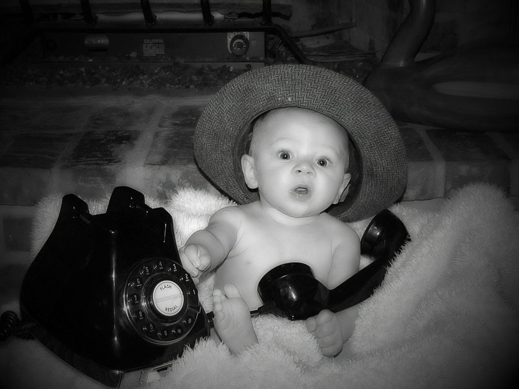 baby playing with old telephone - black and white